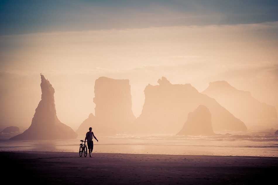 Bicyclist walking on Bandon Beach, Oregon